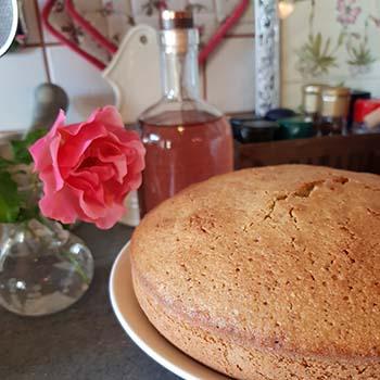 Sciogliere il burro e unirlo allo zucchero. Aggiungere le uova, uno alla volta. Unire il succo e la scorza di mezza arancia. Tritare finemente i pistacchi e le mandorle, unirli all'impasto insieme alla farina, alla fecola e al lievito setacciati. Cuocere in una teglia imburrata e infarinata di 21 cm per 40 minuti a 180 °C. Preparare la glassa: stemperare lo zucchero a velo con l'acqua alle rose e l'acqua naturale. Io ho aggiunto una goccia di colorante alimentare rosa per dare un po' di colore alla glassa. Versare la glassa sulla torta e decorare subito con pistacchi tritati e petali di rosa.